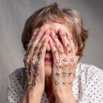 starsza kobieta zasłania oczy